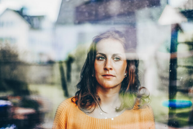 Young woman looks thoughtfully through the window